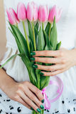 Χέρια γυναικών με το πράσινο μανικιούρ που κρατά τις ρόδινες τουλίπες, κινηματογράφηση σε πρώτο πλάνο στοκ εικόνες