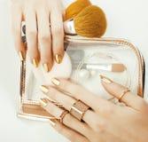 Χέρια γυναικών με το χρυσό μανικιούρ και πολλά δαχτυλίδια που κρατούν τις βούρτσες, makeup μοντέρνο, καθαρό στενό επάνω ροζ ουσία Στοκ Εικόνες