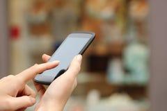 Χέρια γυναικών που αγοράζουν on-line με ένα έξυπνο τηλέφωνο Στοκ Φωτογραφίες