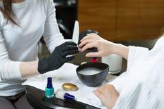 Χέρια γυναικών που λαμβάνουν το μανικιούρ και τη διαδικασία προσοχής καρφιών κοντά επάνω Στοκ Εικόνα