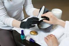 Χέρια γυναικών που λαμβάνουν το μανικιούρ και τη διαδικασία προσοχής καρφιών κοντά επάνω Στοκ Εικόνες