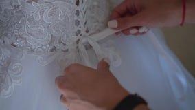 Χέρια γυναικών που δένονται πίσω από το σχοινί στο φόρεμα Οι αμοιβές της νύφης απόθεμα βίντεο