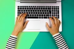 Χέρια γυναικών που δακτυλογραφούν στο πληκτρολόγιο σημειωματάριων στο ζωηρόχρωμο υπόβαθρο Στοκ Εικόνες