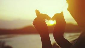 Χέρια γυναικών που διαμορφώνουν μια καρδιά στο καταπληκτικό ηλιοβασίλεμα πέρα από τη θάλασσα στο τροπικό νησί κίνηση αργή 1920x10 φιλμ μικρού μήκους