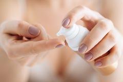 Χέρια γυναικών που εφαρμόζουν την ενυδατική κρέμα στο δέρμα της στοκ φωτογραφία με δικαίωμα ελεύθερης χρήσης