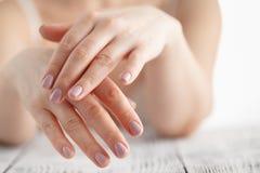 Χέρια γυναικών που εφαρμόζουν την ενυδατική κρέμα στο δέρμα της στοκ φωτογραφίες