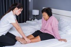 Χέρια γυναικών που κάνουν το μασάζ στα πόδια πόνου ηλικιωμένων γυναικών στο κρεβάτι Στοκ εικόνες με δικαίωμα ελεύθερης χρήσης