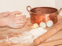 Χέρια γυναικών που κάνουν pasrty με τη ζύμη, αλεύρι, κομμάτι του βουτύρου, π.χ. Στοκ Φωτογραφία