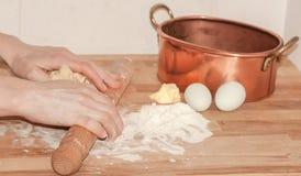 Χέρια γυναικών που κάνουν pasrty με τη ζύμη, αλεύρι, κομμάτι του βουτύρου, π.χ. Στοκ φωτογραφία με δικαίωμα ελεύθερης χρήσης