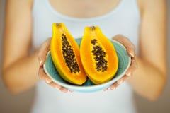 Χέρια γυναικών που κρατούν μερικά papayas, αισθησιακός πυροβολισμός στούντιο στοκ φωτογραφίες