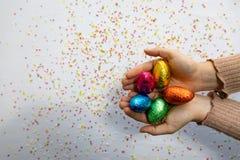 Χέρια γυναικών που κρατούν τα ζωηρόχρωμα αυγά Πάσχας σοκολάτας με το άσπρο υπόβαθρο και το ζωηρόχρωμο θολωμένο κομφετί στοκ φωτογραφία με δικαίωμα ελεύθερης χρήσης