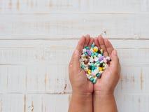 Χέρια γυναικών που κρατούν τα ζωηρόχρωμα χάπια στο άσπρο ξύλινο υπόβαθρο Χ στοκ φωτογραφίες με δικαίωμα ελεύθερης χρήσης