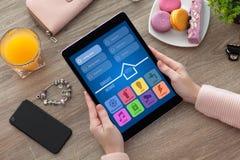 Χέρια γυναικών που κρατούν την ταμπλέτα με app το έξυπνο σπίτι και το τηλέφωνο Στοκ εικόνα με δικαίωμα ελεύθερης χρήσης