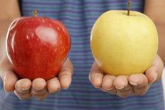 Χέρια γυναικών που κρατούν τη Apple και το πορτοκάλι στα χέρια της Στοκ εικόνα με δικαίωμα ελεύθερης χρήσης
