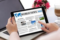 Χέρια γυναικών που κρατούν τον υπολογιστή ταμπλετών με app την οθόνη παγκόσμιων ειδήσεων Στοκ Φωτογραφίες