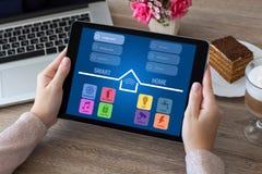 Χέρια γυναικών που κρατούν τον υπολογιστή ταμπλετών με app το έξυπνο σπίτι Στοκ Εικόνες