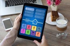 Χέρια γυναικών που κρατούν τον υπολογιστή ταμπλετών με app το έξυπνο σπίτι Στοκ εικόνα με δικαίωμα ελεύθερης χρήσης