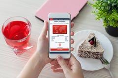 Χέρια γυναικών που κρατούν το άσπρο τηλέφωνο με app το σε απευθείας σύνδεση καφέ αγορών Στοκ Φωτογραφία