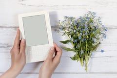 Χέρια γυναικών που κρατούν το άσπρο ebook με τα λουλούδια στο υπόβαθρο Στοκ φωτογραφία με δικαίωμα ελεύθερης χρήσης