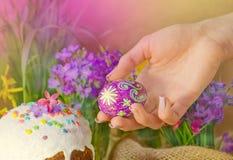 Χέρια γυναικών που κρατούν το αυγό Πάσχας Πίνακας που διακοσμεί για τις διακοπές Πάσχας Στοκ εικόνες με δικαίωμα ελεύθερης χρήσης