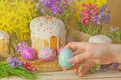 Χέρια γυναικών που κρατούν το αυγό Πάσχας Πίνακας που διακοσμεί για τις διακοπές Πάσχας Στοκ Εικόνα