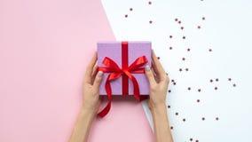 Χέρια γυναικών που κρατούν το δώρο με το τόξο στο ρόδινο και άσπρο υπόβαθρο με το διάστημα αντιγράφων Επίπεδος βάλτε στοκ εικόνες