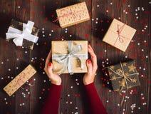 Χέρια γυναικών που κρατούν το κιβώτιο δώρων διακοπών Χριστουγέννων στο διακοσμημένο εορταστικό πίνακα Στοκ φωτογραφία με δικαίωμα ελεύθερης χρήσης