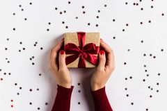 Χέρια γυναικών που κρατούν το κιβώτιο δώρων διακοπών Χριστουγέννων στο διακοσμημένο εορταστικό πίνακα Στοκ Φωτογραφίες