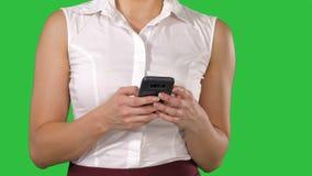 Χέρια γυναικών που κρατούν το τηλέφωνο κυττάρων σε μια πράσινη οθόνη, κλειδί χρώματος απόθεμα βίντεο