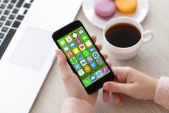 Χέρια γυναικών που κρατούν το τηλέφωνο με το σημειωματάριο εικονιδίων εγχώριας οθόνης apps Στοκ Εικόνα