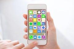 Χέρια γυναικών που κρατούν το τηλέφωνο με τα εικονίδια εγχώριας οθόνης apps Στοκ φωτογραφίες με δικαίωμα ελεύθερης χρήσης