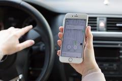 Χέρια γυναικών που κρατούν το iPhone 6S με το ταξί Uber εφαρμογής Στοκ Εικόνα