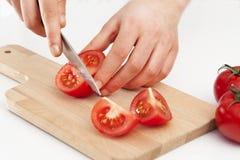 Χέρια γυναικών που κόβουν την ντομάτα Στοκ Φωτογραφία