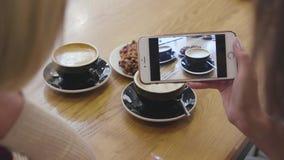 Χέρια γυναικών που παίρνουν τη φωτογραφία τροφίμων στο κινητό τηλέφωνο στην κινηματογράφηση σε πρώτο πλάνο καφέδων απόθεμα βίντεο