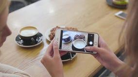 Χέρια γυναικών που παίρνουν τη φωτογραφία τροφίμων στο κινητό τηλέφωνο στην κινηματογράφηση σε πρώτο πλάνο καφέδων φιλμ μικρού μήκους