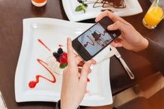 Χέρια γυναικών που παίρνουν τις εικόνες του επιδορπίου στο πιάτο που χρησιμοποιεί το smartphone Στοκ Εικόνες