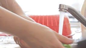 Χέρια γυναικών που πλένουν το σκεύος για την κουζίνα κάτω από το ρεύμα νερού φιλμ μικρού μήκους