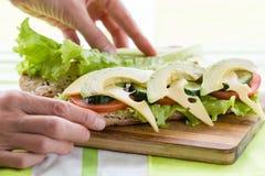 Χέρια γυναικών που προετοιμάζουν το υγιές πρόγευμα που κατασκευάζει το εύγευστο σάντουιτς Στοκ φωτογραφία με δικαίωμα ελεύθερης χρήσης