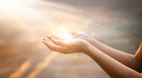 Χέρια γυναικών που προσεύχονται στο υπόβαθρο ηλιοβασιλέματος στοκ εικόνες