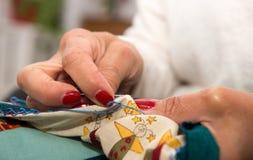 Χέρια γυναικών που ράβουν για το τέρμα ένα πάπλωμα Στοκ Φωτογραφία