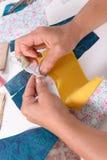 Χέρια γυναικών που ράβουν για το τέρμα ένα πάπλωμα Στοκ Εικόνες