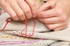 Χέρια γυναικών που ράβουν με το muline Στοκ Φωτογραφίες
