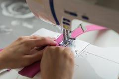Χέρια γυναικών που ράβουν στη ράβοντας μηχανή Στοκ Εικόνες