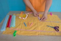 Χέρια γυναικών που ράβουν το κίτρινο ύφασμα υπαίθρια Στοκ εικόνες με δικαίωμα ελεύθερης χρήσης
