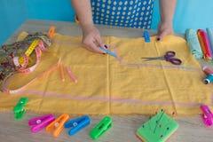 Χέρια γυναικών που ράβουν το κίτρινο ύφασμα υπαίθρια Στοκ φωτογραφία με δικαίωμα ελεύθερης χρήσης