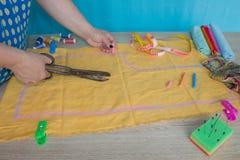 Χέρια γυναικών που ράβουν το κίτρινο ύφασμα υπαίθρια Στοκ Φωτογραφίες