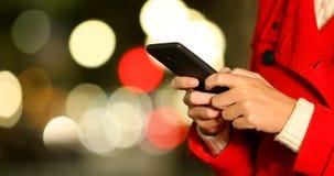 Χέρια γυναικών που στο τηλέφωνο σε μια χειμερινή νύχτα απόθεμα βίντεο