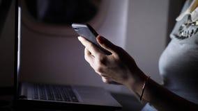 Χέρια γυναικών που στο smartphone στο επιβατηγό αεροσκάφος απόθεμα βίντεο