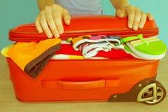 Χέρια γυναικών που συσκευάζουν την ουσία στη βαλίτσα στο σπίτι Βαλίτσα με τα πράγματα για τα έξοδα των πραγμάτων θερινών διακοπών Στοκ Εικόνα
