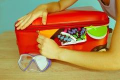 Χέρια γυναικών που συσκευάζουν την ουσία στη βαλίτσα στο σπίτι Βαλίτσα με τα πράγματα για τα έξοδα των πραγμάτων θερινών διακοπών Στοκ Εικόνες